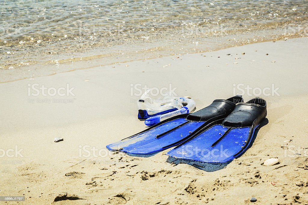 Scuba diving mask and fins on sandy beach stock photo