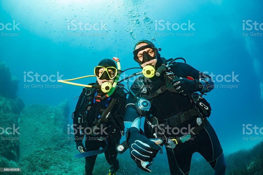 Scuba diving    Underwater  Couple scuba divers in blue stock photo