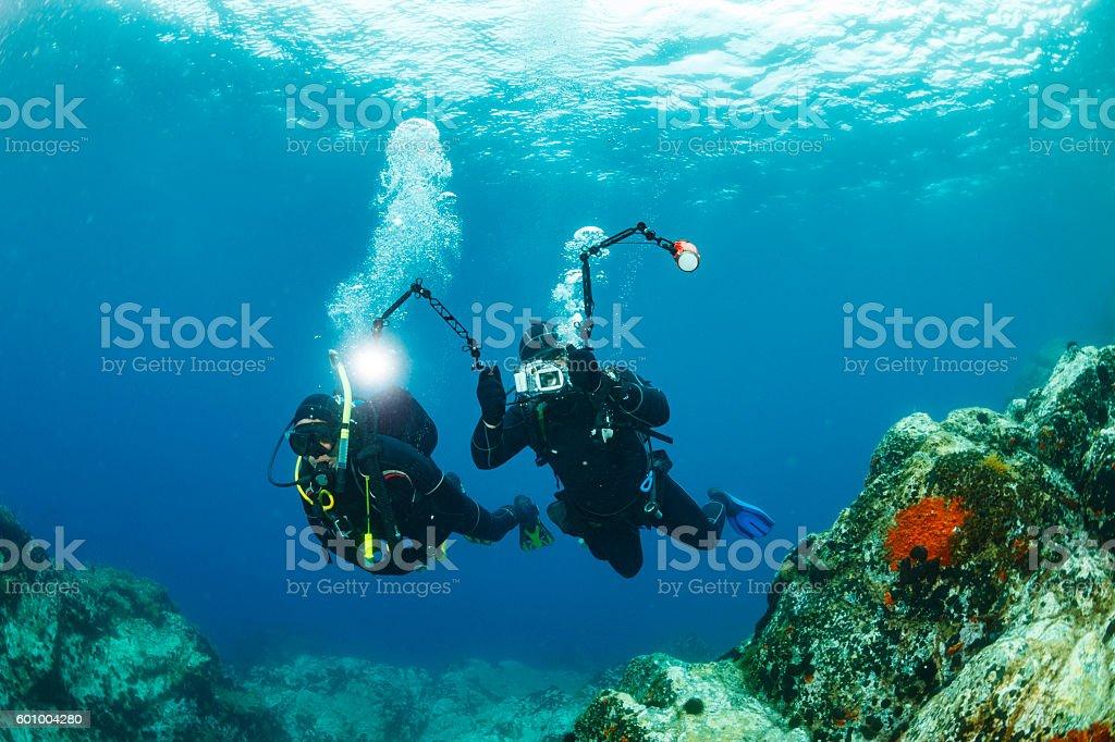 Scuba diving   Underwater photographer  Team of scuba divers stock photo