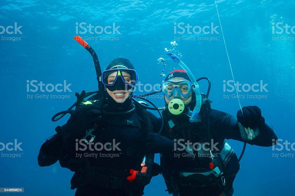 Scuba diving    Underwater scene with two scuba diver in blue stock photo