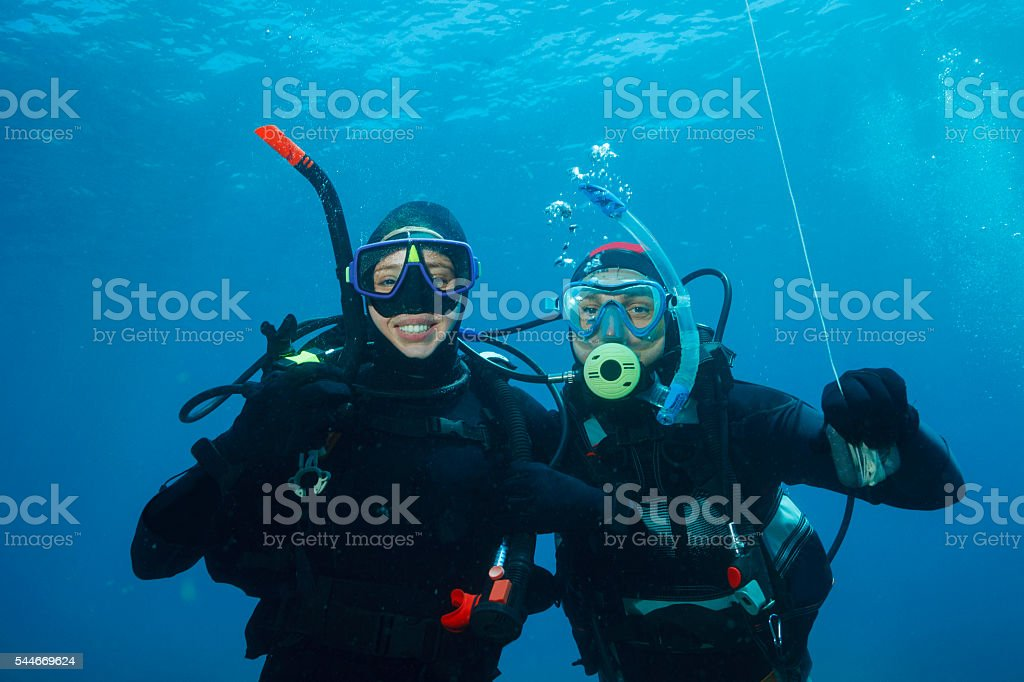 Scuba diving    Underwater scene with two scuba diver in blue stock photo