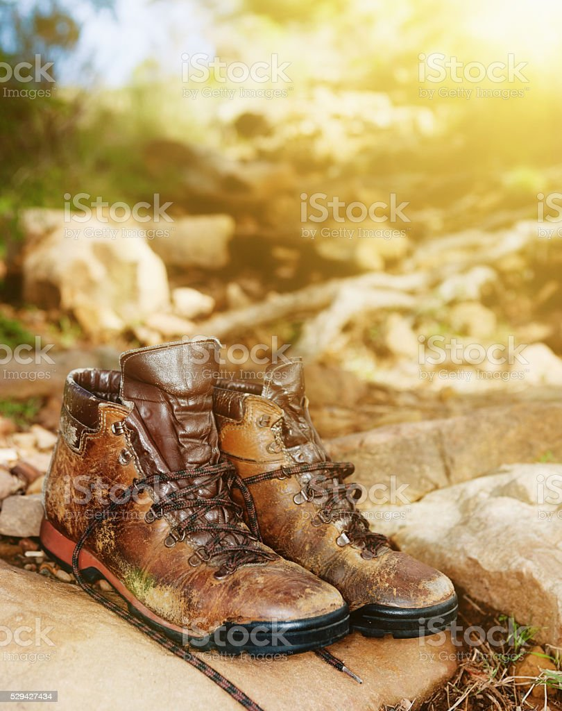 Scuffed and worn but reliable hiking boots resting on rock stock photo