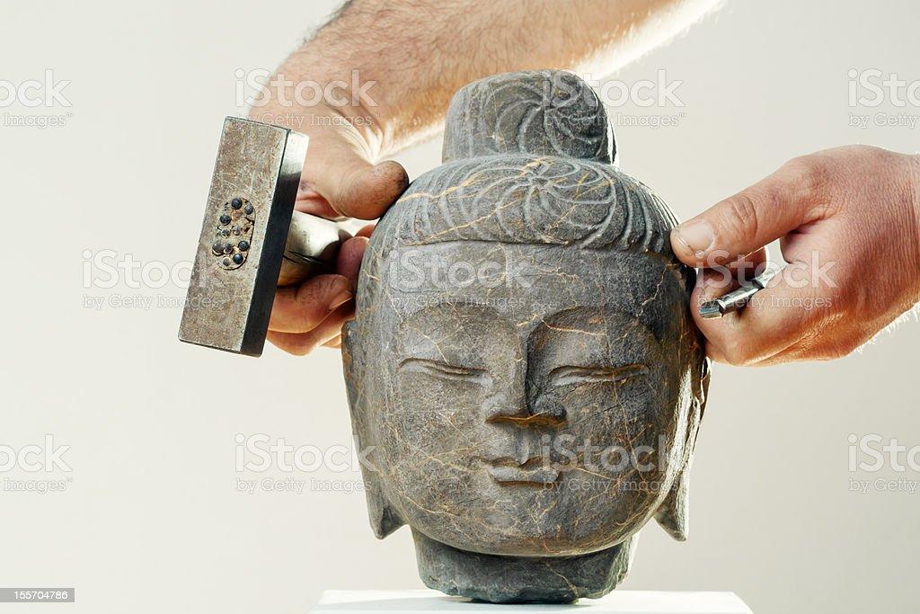 Sculptor put stone head of Buddha on marble pedestal stock photo