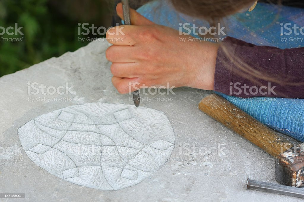 Sculptot making ornament on a stone monolith royalty-free stock photo