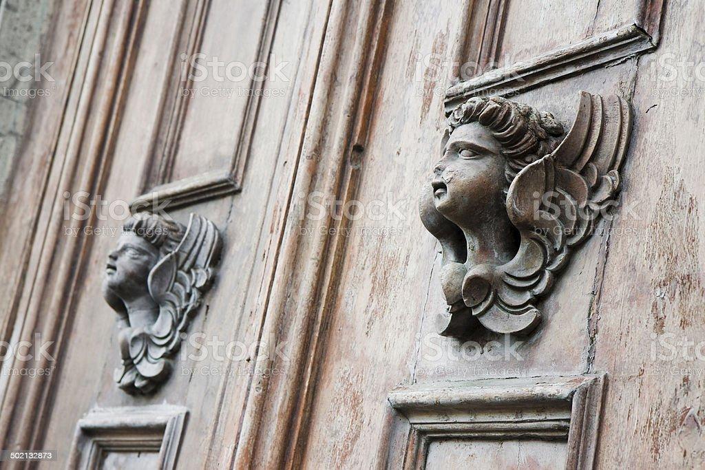 Sculpture of an angel on a wooden door stock photo