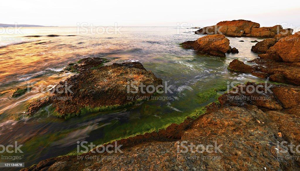 Sea and rocks at sunset stock photo