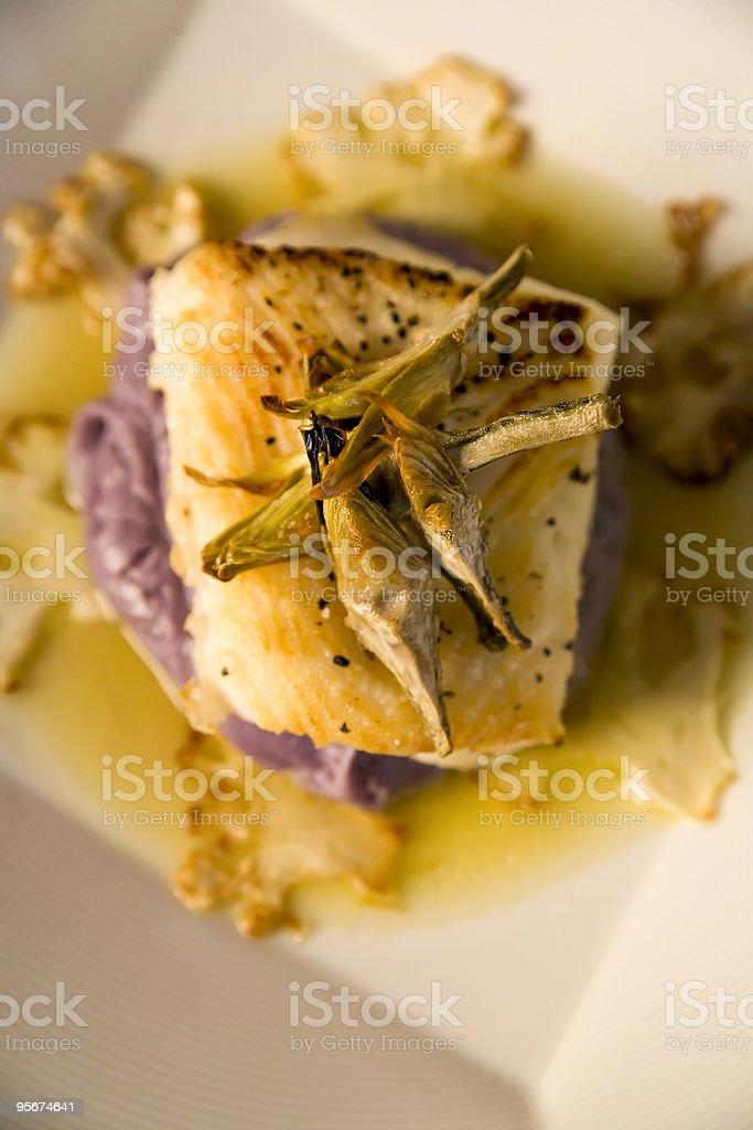 Sea bass on a bed of purple potato puree royalty-free stock photo