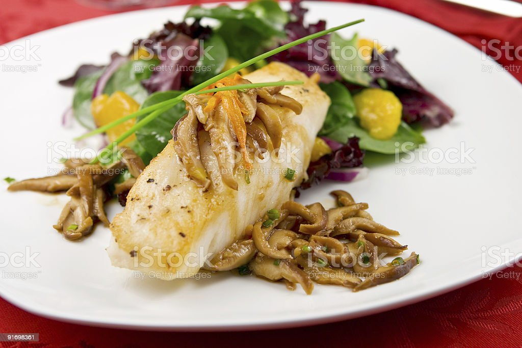 Sea bass with mushrooms and salad royalty-free stock photo