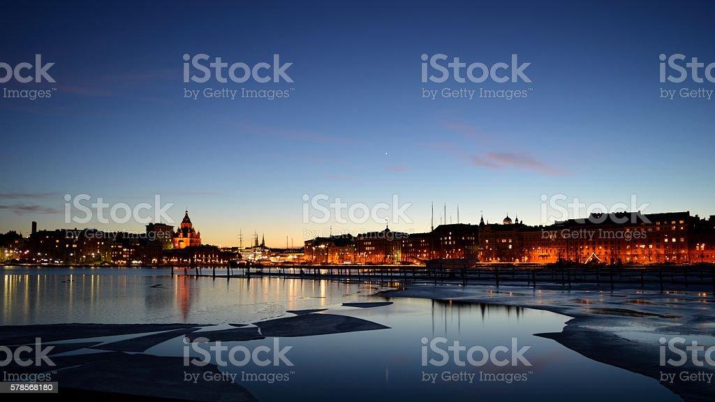 Sea bay at dusk, water, ice sheets, buildings, city lights stock photo