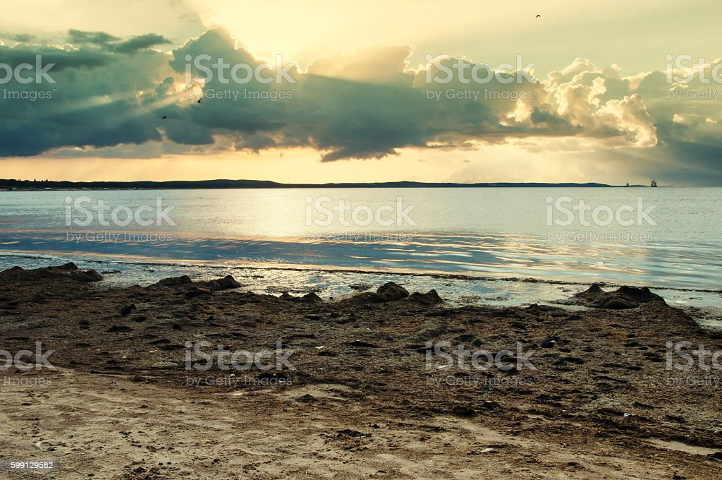 sea, beach and light behind the clouds stock photo