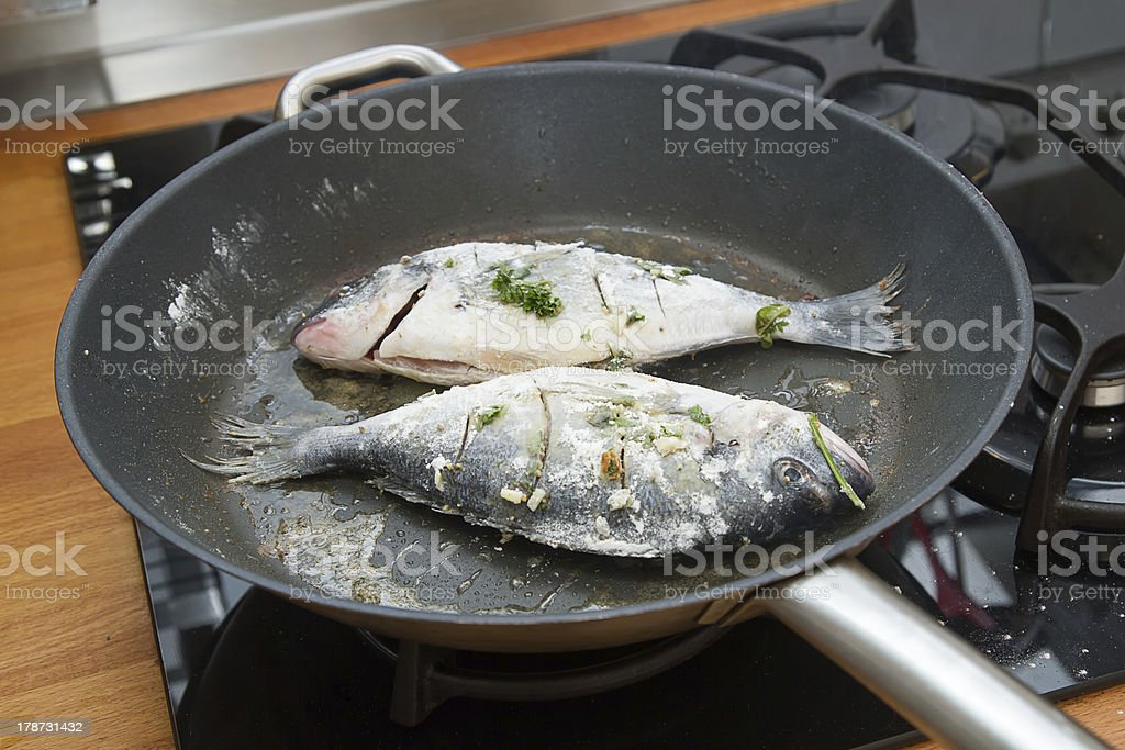 Sea bream cooking in frying pan royalty-free stock photo