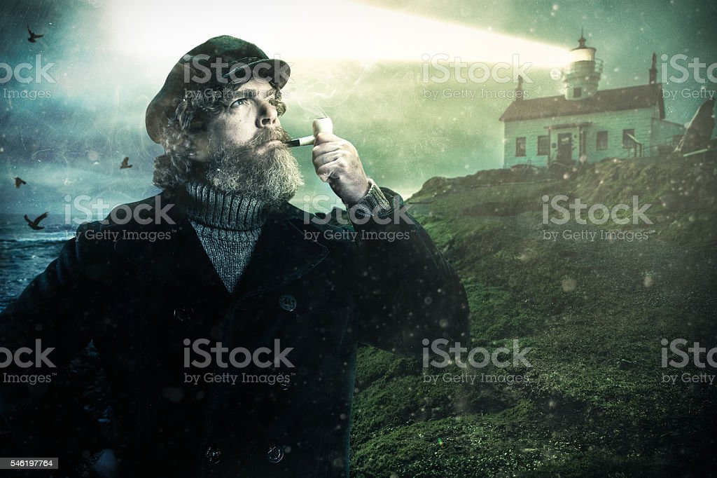 Sea Captain with Smoking Pipe and Lighthouse on the coast stock photo