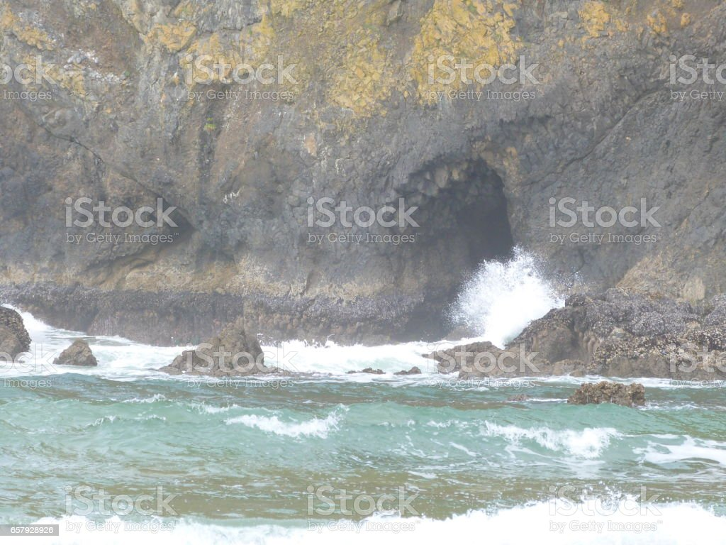 Sea Cave opening with teal waves stock photo