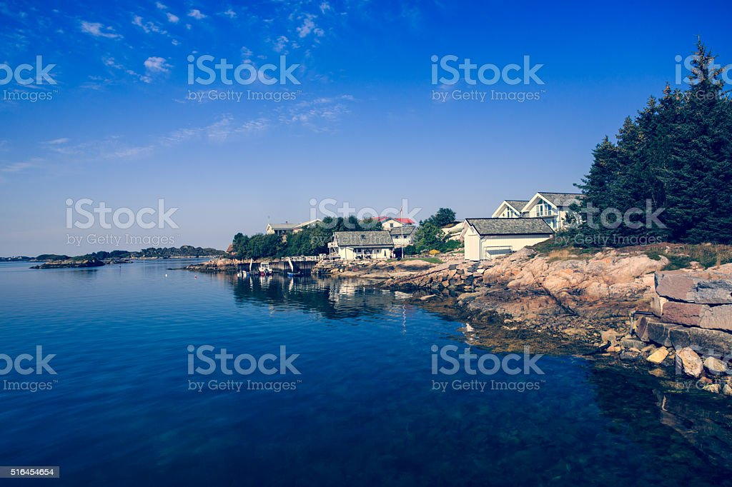Sea cliffs and houses on the sea in Norway stock photo