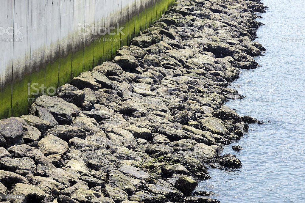 sea dock with wall and rocks stock photo