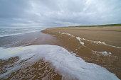 Sea foam on the shore, Sakhalin Island, Russia.
