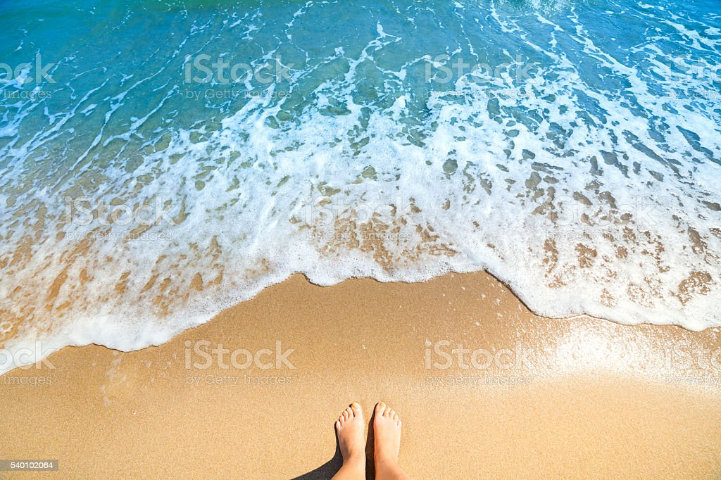Sea foam, waves and naked feet on a sand beach stock photo