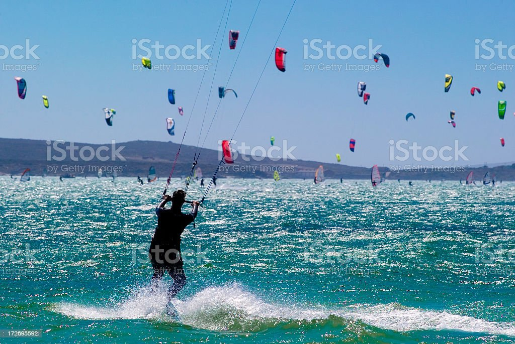 A sea full of kitesurfers with one seen from the rear stock photo