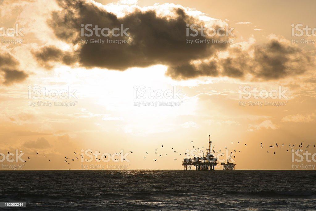 Sea Gulls Fly in Front of Oil Platform royalty-free stock photo