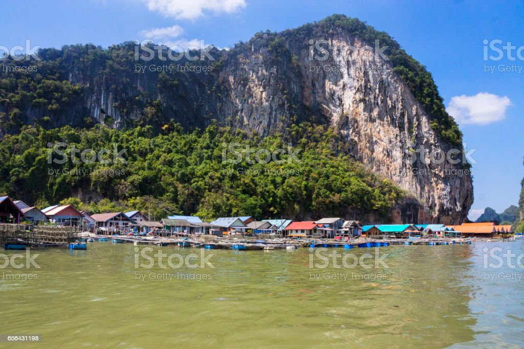 Sea Gypsy village at the foot of a huge mountain, view from the sea stock photo
