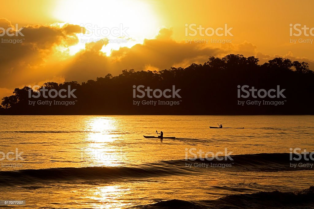 Sea kayak adventure with moody sunrise stock photo