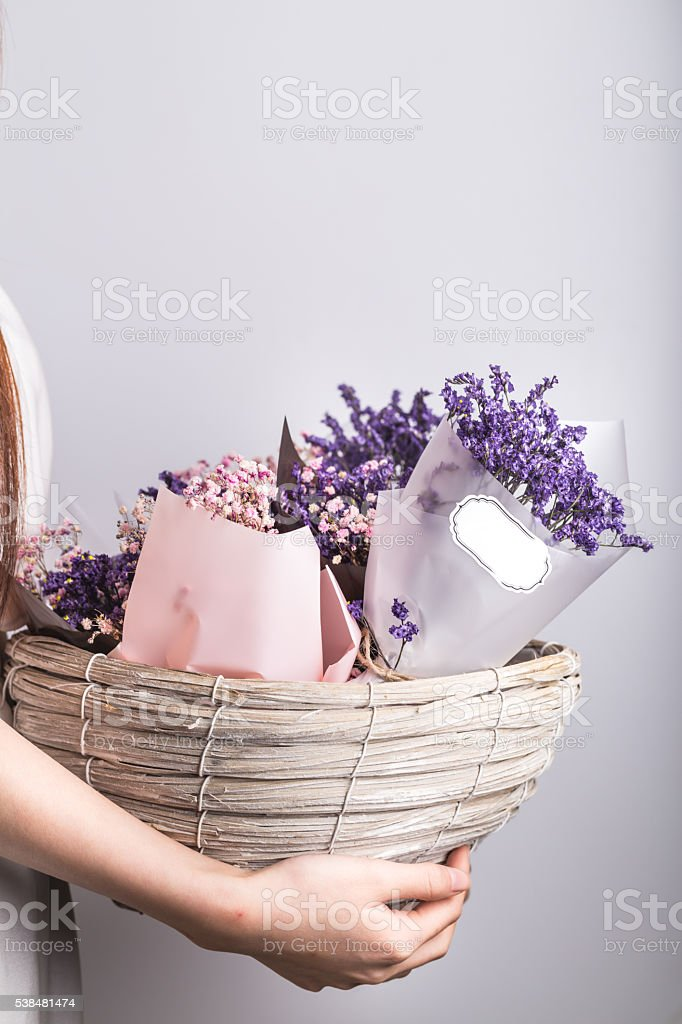 sea lavender wrapped in basket hold by hand stock photo