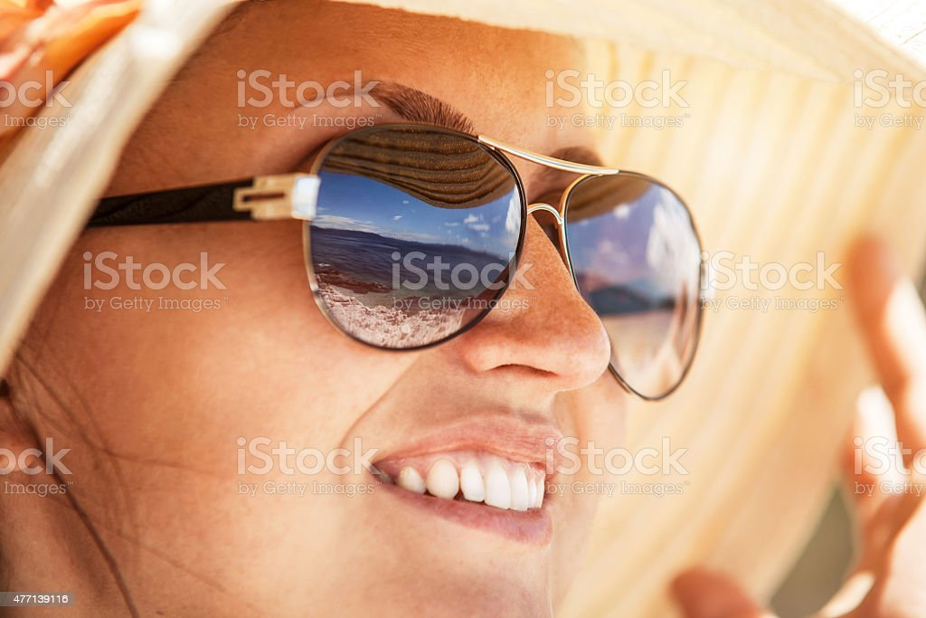 Sea mirror in woman sun glasses stock photo