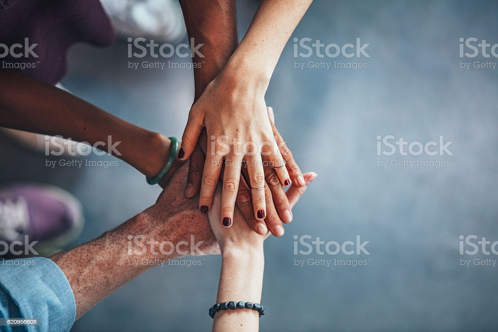 Sea of hands showing unity and teamwork stock photo