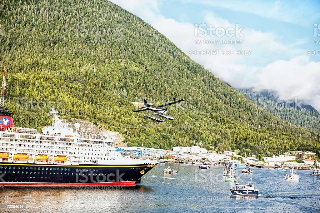 Sea plane flying over cruise ship docked in Ketchikan, Alaska stock photo