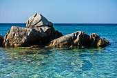 Sea rocks and turquoise water near sandy beach at morning