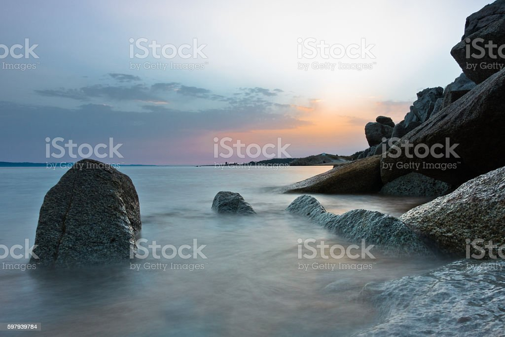 Sea rocks on sandy beach at sunset in Sithonia, Chalkidiki stock photo