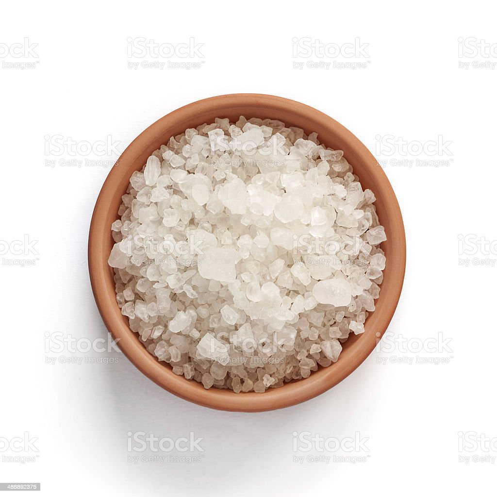 Sea salt in bowl on white background stock photo