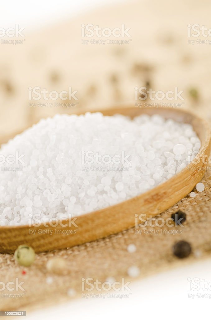 Sea salt in the wooden bowl with pepper corns royalty-free stock photo