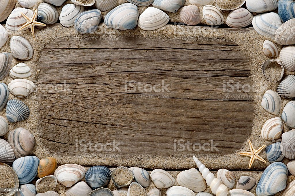 Sea shell frame and sand on old wood stock photo