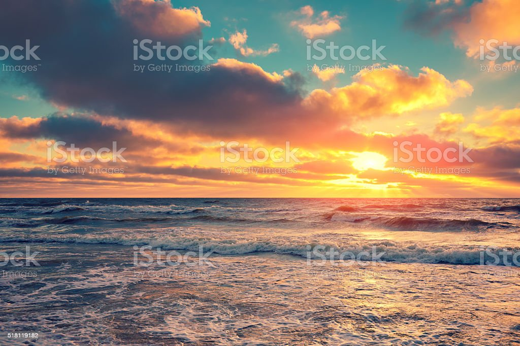 Sea shore at sunset with cloudy sky stock photo