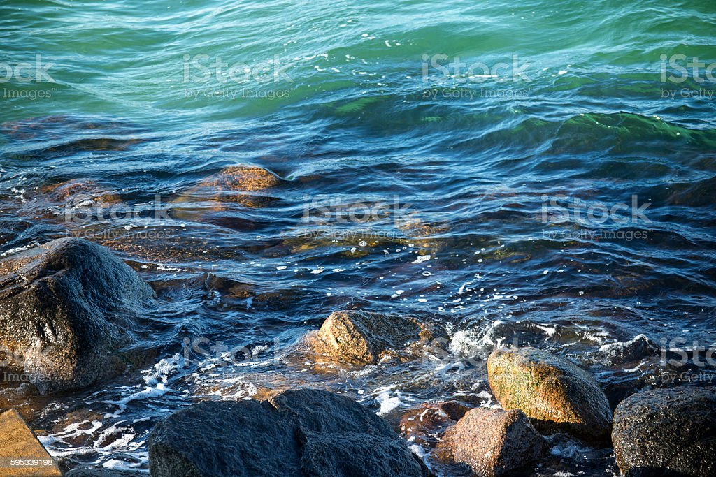 sea shore with stones in the gentle surf stock photo