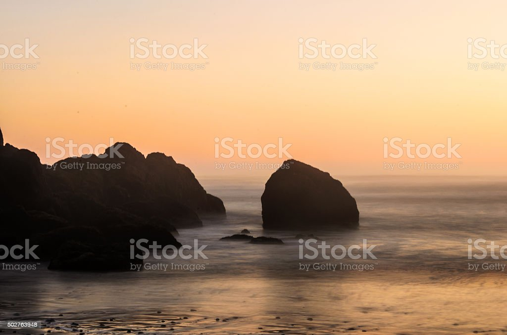Sea Stack Silhouette at sunset in the Pacific Northwest stock photo