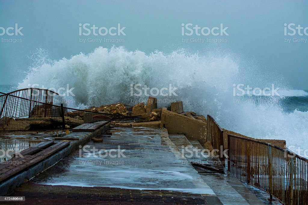 Sea storm waves crashing and splashing against pier stock photo