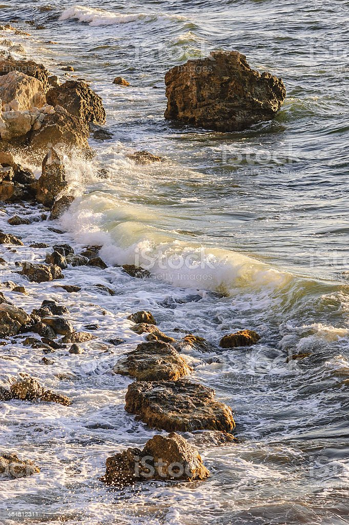 Sea tide in rays of sunset stock photo
