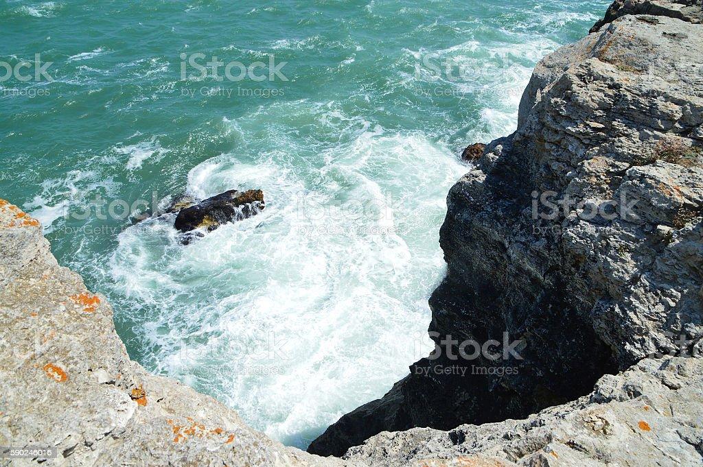 Sea water splashing onto vertical cliffs stock photo