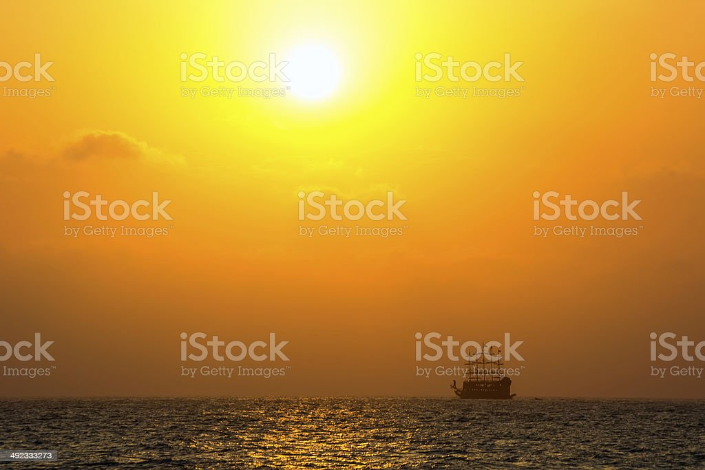 Sea with silhouette of the ancient ship at sunset royalty-free stock photo