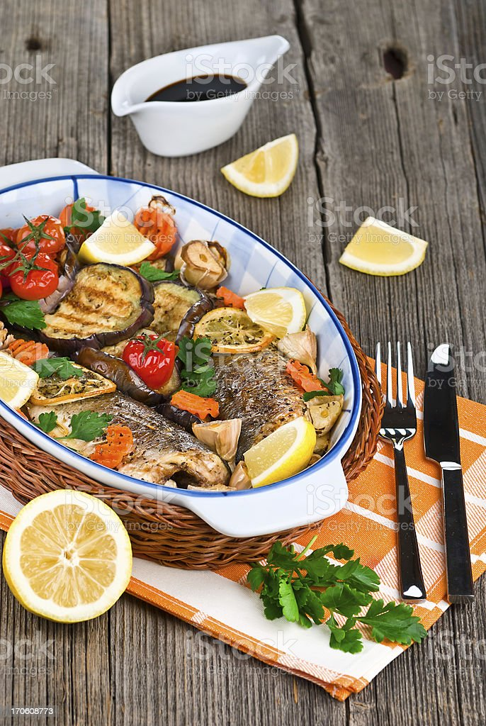 seabass fish baked with vegetables, herbs and lemon royalty-free stock photo