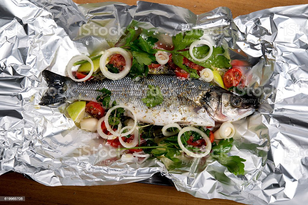 seabass in tin-foil ready to baked stock photo