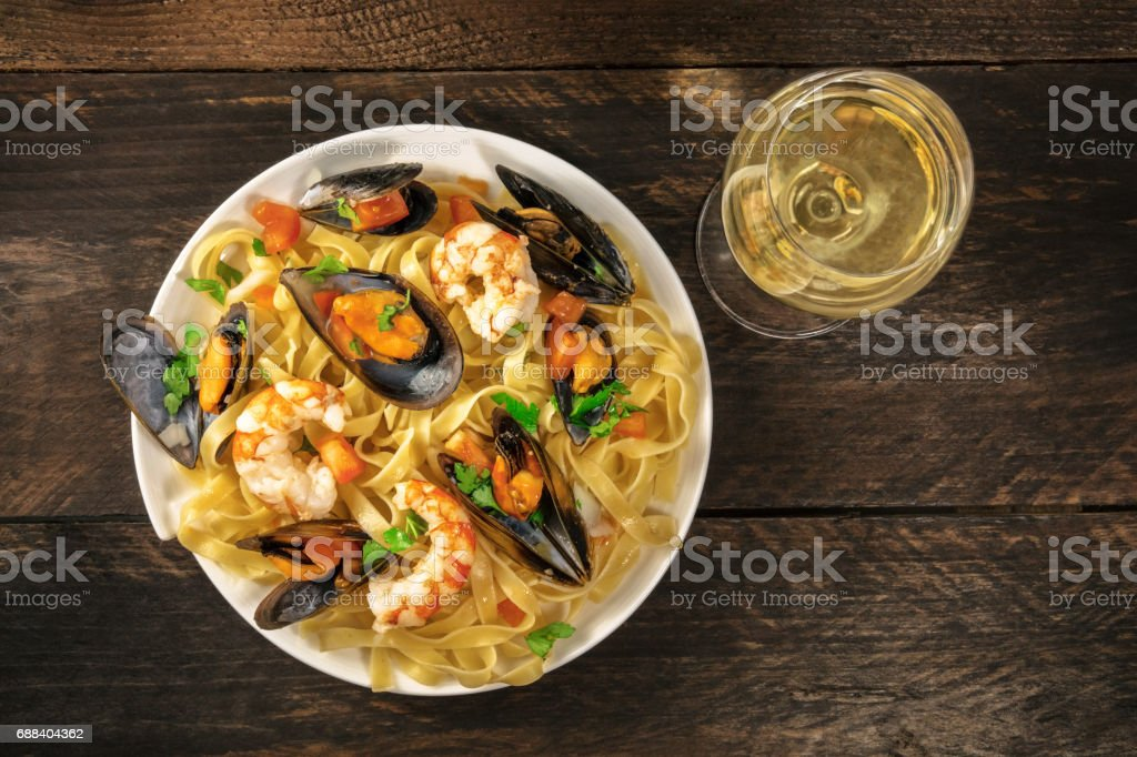 Seafood pasta with mussels, shrimps, and white wine stock photo