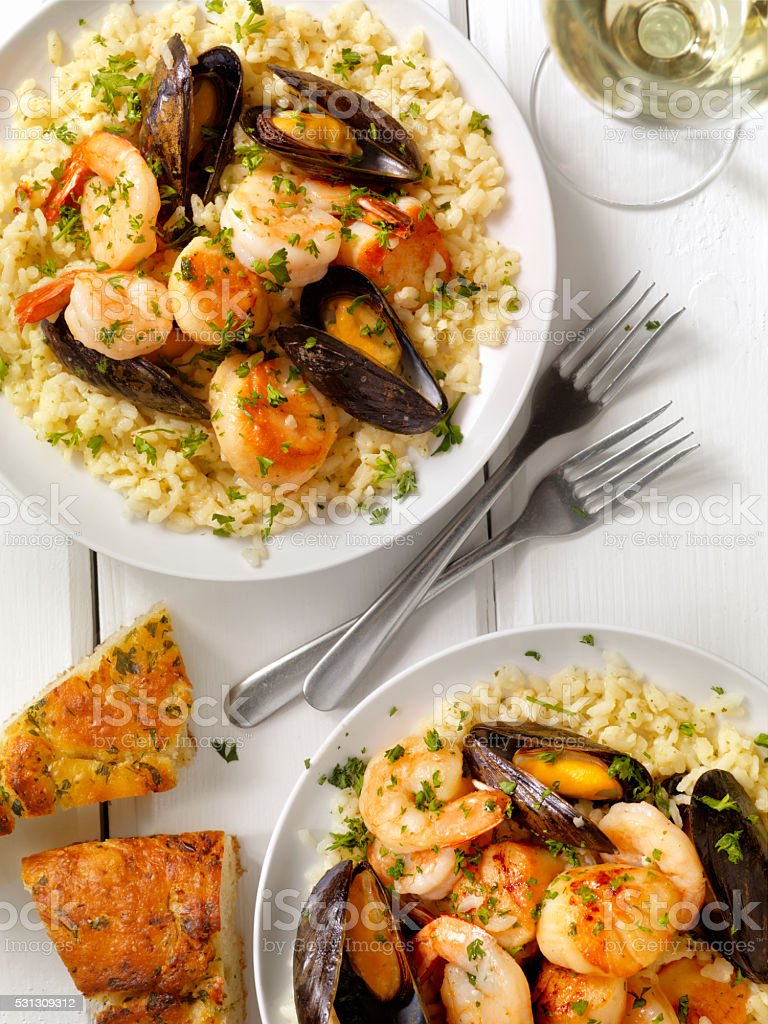 Seafood Risotto with Fresh Parsley and Focaccia Bread stock photo