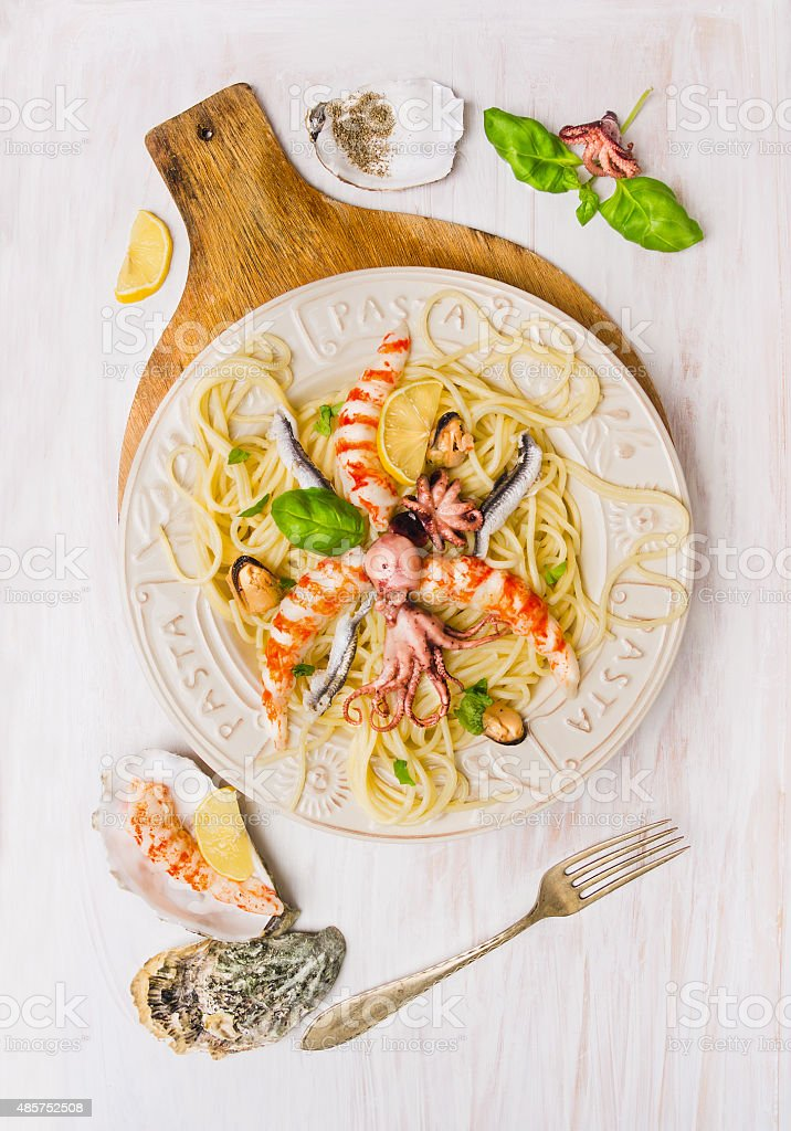 seafood spaghetti on white wooden background, top view stock photo