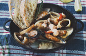 Seafood Stew in Saucepan on dark wood background