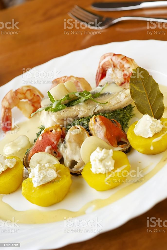 Seafood with spinach, yellow potatoes and cream sauce royalty-free stock photo