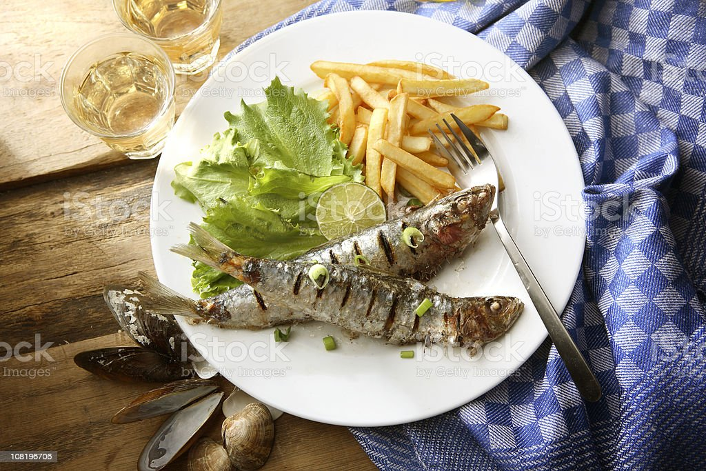 Sardines with French Fries on Plate stock photo