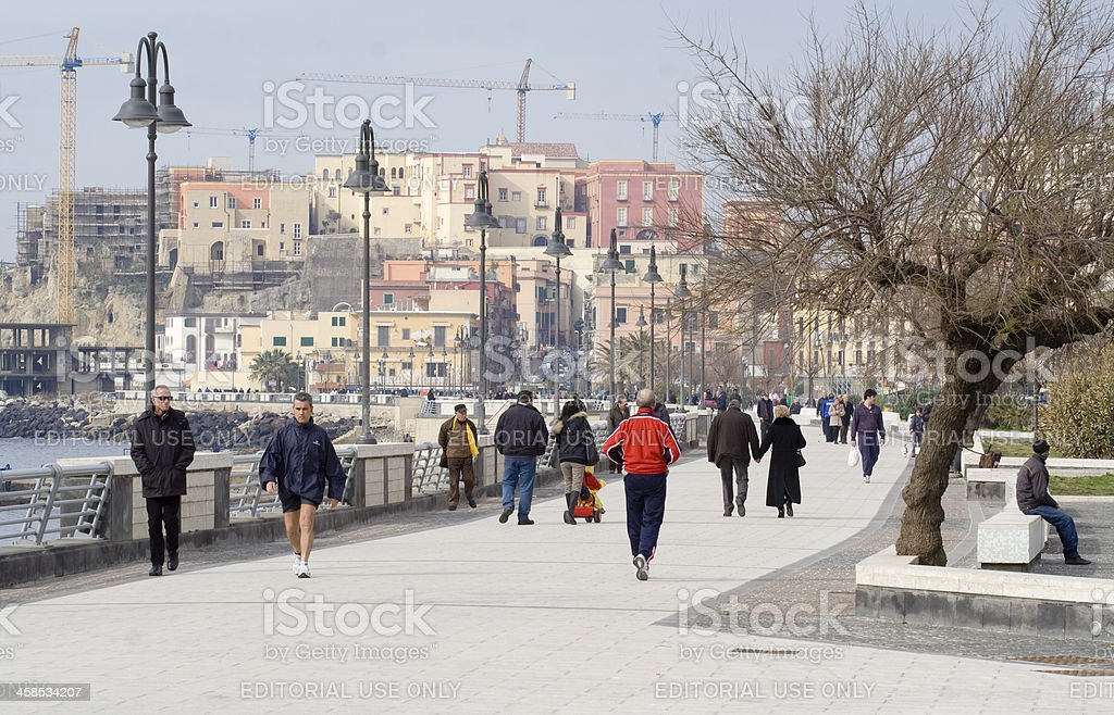 Seafront with people walking in Pozzuoli, Naples, Campania, Italy, royalty-free stock photo